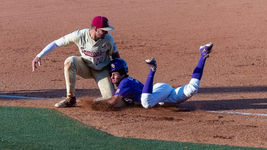 LSU's Giovanni DiGiacomo dives back to third and is picked off by the tag from Florida State's Drew Mendoza during Game 2 of the NCAA college baseball super regional tournament in Baton Rouge, La., Sunday, June 9, 2019. (Scott Clause/The Daily Advertiser via AP)