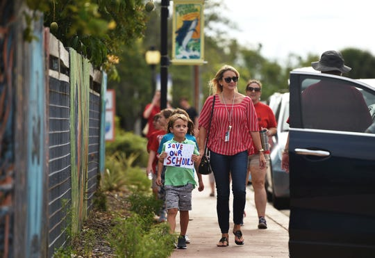 "Palm City Elementary guidance counselor Kate Bradley, of Stuart, walks with her son, Hudson Bradley, 5, and daughter, Clara Bradley (not pictured), 8, to join a crowd gathering to march in support of reforms to Florida's public education system Wednesday, May 15, 2019, in Stuart. ""I had to come,"" Kate Bradley said. ""I think the biggest thing is — being in mental health — I see the impact of all the different decisions that are made...testing: all the anxiety that the kids experience, all of the pressure on the teachers because their pay is based upon how the students in their classrooms perform,"" she added."