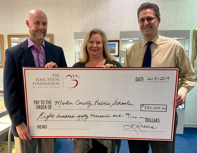 Education Foundation of Martin County board members Tyson Waters, left, Kelly Bond Pelletier and Michael Moehring with an $850,000 check representing the value of financial and program support provided by the Education Foundation to Martin County public schools during the 2018-19 school year.