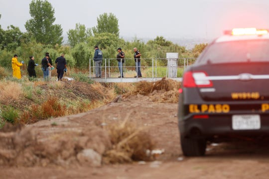 El Paso police and medical examiner investigators walk across a bridge near Upper Valley Road to examine the body of a man found in the canal on Monday.