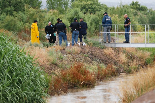 El Paso police and medical examiner staff walk across a bridge near the 6000 block of Upper Valley Road to examine the body of a man found in the canal on Monday.