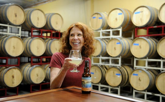 Karen Stewart, co-owner of Four Brix Winery in Ventura, poses with a glass of persimmon-lavender cider from Pier City Cider. The hard-cider label is being made under the same roof by her husband, Four Brix winemaker Gary Stewart. It will launch June 21.