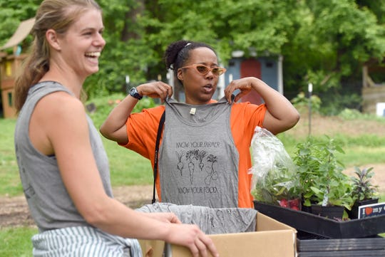 Emma Jagoz, left, founder and co-owner of Moon Valley Farm, smiles as Pam Suarez, of Windsor Mill, holds up a tank top during a plant sale, which the farm holds on Saturdays during the spring.