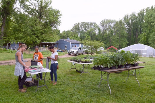 In a May 18, 2019 photo, Emma Jagoz, left, founder and co-owner of Moon Valley Farm, helps customers Pam Suarez, center, of Windsor Mill, and Cathy Foster, of Pikesville, during a plant sale, which the farm holds on Saturdays during the spring.