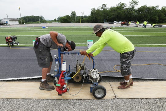 Brad Guckert, left, and Juan Mendez of The Motz Group install turf at West Muskingum's football field recently. The pair are using a mobile sewing machine to assemble long strips of turf into the field.