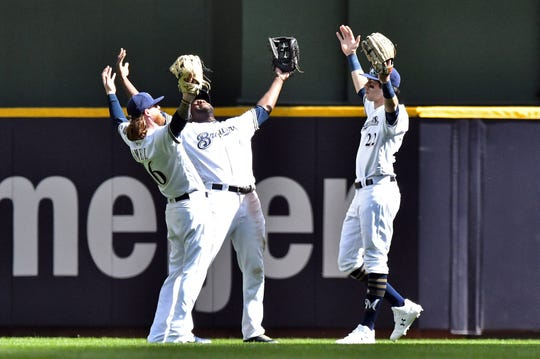Ben Gamel, Lorenzo Cain and Christian Yelich celebrate a win.