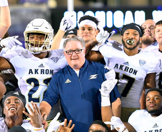 Akron players and coach Terry Bowden celebrate after beating Northwestern during the 2018 season.