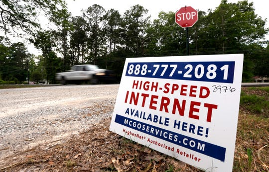 A car drives past a sign advertising high-speed internet service near Starkville, Miss.