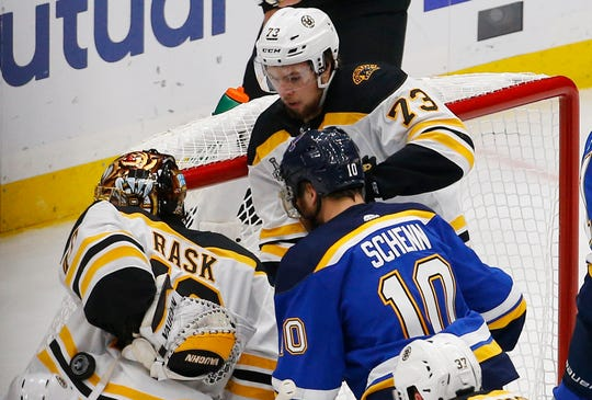 The puck rolls down the back of Boston Bruins goaltender Tuukka Rask aftter defenseman Charlie McAvoy helped keep it out of the net.