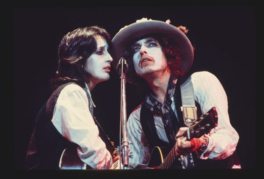 Folk icons Joan Baez, left, and Bob Dylan performing together during the Rolling Thunder Revue tour, which spanned 57 concerts between 1975 and 1976.