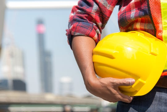 Worker holding a yellow safety hardhat.