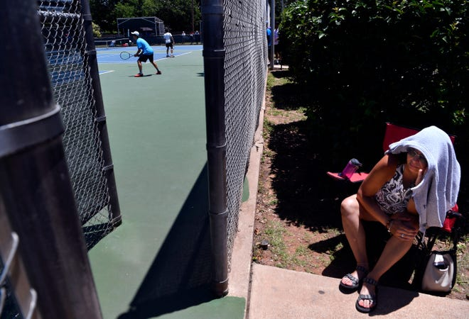 Yaremi Rivero watches Christopher Cequea play as singles match as others also play at Rose Park Tennis Center during Tuesday's Texas Slam tennis tournament. The tournament brought more than 1,000 players to the city and will continue through Saturday.