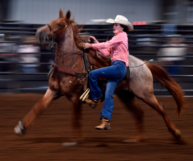 Josie McMahon of Richards jumps off her horse during goat tying at the Texas High School Rodeo Association State Finals at the Taylor County Expo Center's livestock barn Tuesday.
