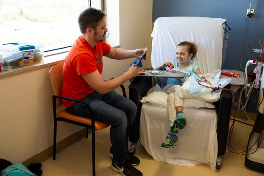 Battle Creek Enquirer reporter Nick Buckley and his daughter, Charlie, play Uno during her dialysis treatment at C.S. Mott Children's Hospital in Ann Arbor on Tuesday, May 16, 2019.