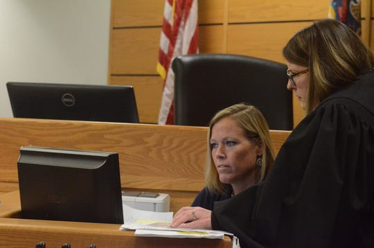 Circuit Court Judge Sarah Lincoln, right, reviews some case material during the hearing with Kelly Jo Irons, court services officer.