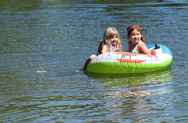 New friends Etta Hovarter, 5, (left) and Olivia Barela, 7, float in a tube at Island Lake Park in Central Kitsap on a warm and sunny Tuesday, June 11, 2019.