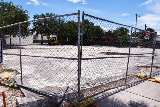 Fencing surrounds the former city-owned parking lot behind Meg O'Malley's Restaurant and Irish Pub, where heavy equipment is now tearing up the asphalt.