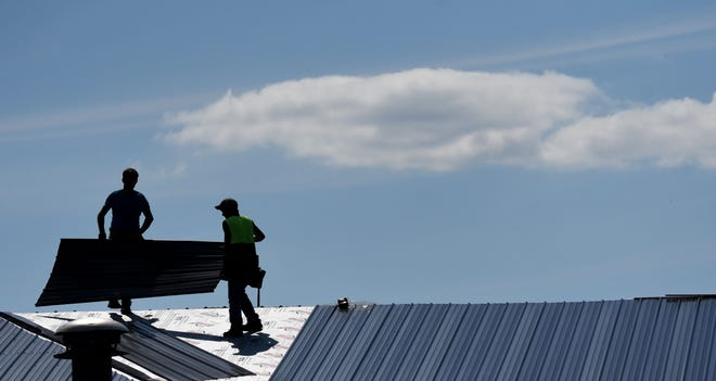 Workers replace the roof on the Avita Building in Crestline on Tuesday afternoon to the backdrop of puffy white clouds and a blue sky.