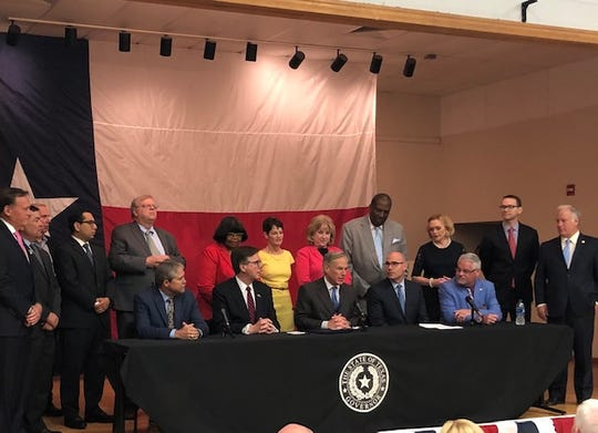Gov. Greg Abbott, flanked by lawmakers, signs legislation to boosting funding for public schools at an Austin elementary school on June 11, 2019.