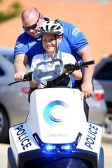 Blake Hegner, 10, of Fort Thomas, smiles as he takes a turn on a Cincinnati Police Segway with Police Officer Finley on Tuesday morning. Hegner was given the opportunity to become 'chief for a day' after Christina Bold, campaign manager for the Leukemia and Lymphoma Society, bet on the activity for a fundraiser through the Matt Haverkamp Foundation. Hegner is in remission for Acute Lymphoblastic Leukemia.