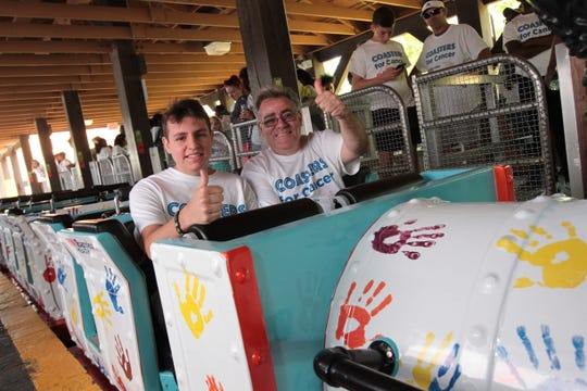 Johnny Volpe, a 17-year-old cancer Survivor from Monroe, Township, and his father, Vinny Volpe, give the thumbs up, as they prepare for the inaugural ride of the Coasters for Cancer campaign.