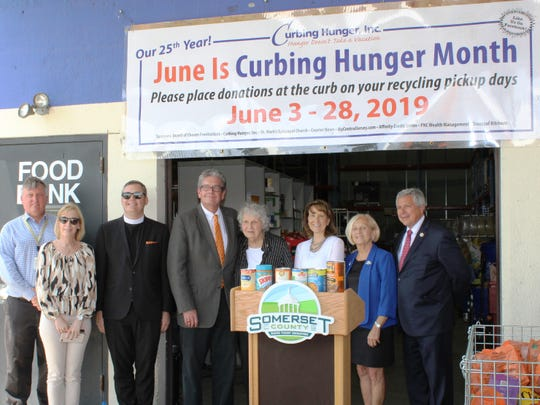 Kicking off the 25th annual Somerset County Curbing Hunger Month food drive are (left to right) Somerset County Recycling Superintendent John Kendzulak; Amp Your Good Customer Service Liaison Nora Knoll; the Rev. Rick Morley of St. Mark's Episcopal Church in the Basking Ridge section of Bernards; Curbing Hunger Inc. Board President Chuck Knill; Food Bank Network Director Marie Scannell; Affinity Foundation Director Judi Meighan; Somerset County Freeholder Deputy Director Patricia Walsh; and state Sen. Kip Bateman.
