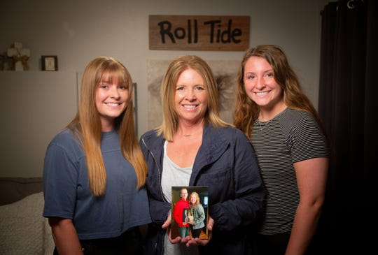 Madison Nelson, her mother Michelle, and sister Grace stand with a photo of their father and husband Mike Nelson Monday, June 10, 2019. Nelson, who passed away two and a half years ago is being honored at a NASCAR race this Fathers Day.