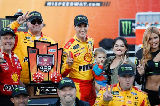 Joey Logano poses with his wife and son with the trophy after winning the FireKeepers Casino 400 at Michigan International Speedway on Monday.