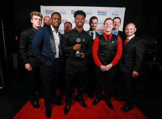 Red Wings center Dylan Larkin, center, poses with Team of the Year Award the Chippewa Valley Football team. The Detroit Free Press Sports Awards recognizes and honors the top athletic accomplishments in Metro Detroit High School Sports and features various awards contests and a special appearance by Detroit Red Wings center, Dylan Larkin Thursday, June 6, 2019 at the Filmore Detroit.