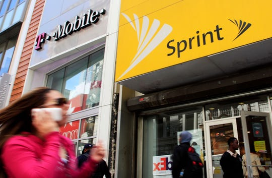 In this April 27, 2010 file photo, a woman using a cell phone walks past T-Mobile and Sprint stores in New York.