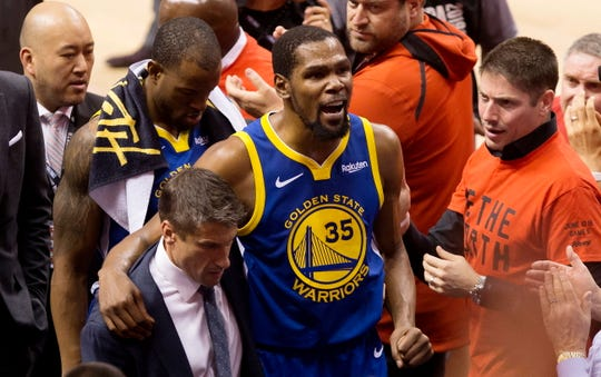 Golden State Warriors forward Kevin Durant leaves the court after suffering an Achilles injury during the first half Monday night.