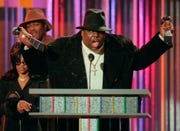 The Notorious B.I.G., who won rap artist and rap single of the year, clutches his awards at the podium during the annual Billboard Music Awards in New York on Dec. 6, 1995.
