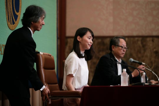 A prominent Hong Kong activist Agnes Chow, center, is helped to her seat before the start of a news conference at Japan National Press Club Monday, June 10, 2019, in Tokyo.