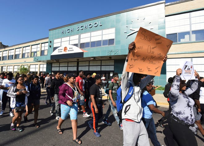 Benton Harbor High School students walk past the front of the high school in Benton Harbor, Mich., Tuesday, June 11, 2019, in preparation of an annual Peace Walk held at the end of the school year.  The Benton Harbor School Board has released a plan aimed at keeping the district's high school open and avoiding a state-threatened shutdown of the struggling district.