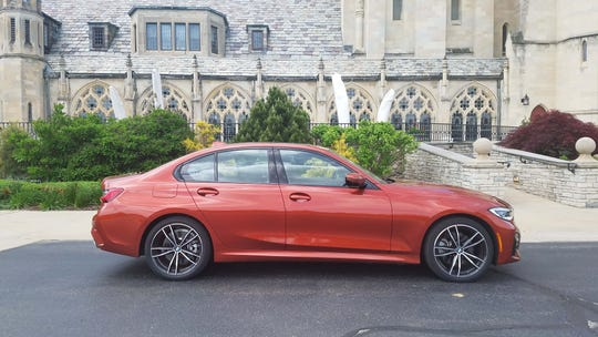 The 2019 BMW 330i sedan's sport coupe roof, long hood, and short overhangs telegraph its rear-wheel-drive, longitudinal engine. The 330i adds AWD for Michigan winters.