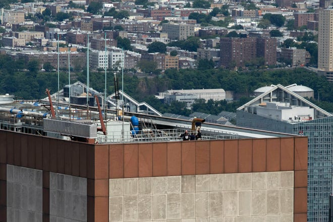 Law enforcement personnel work on the roof of the AXA Equitable building, Tuesday, June 11, 2019 in New York. A helicopter crashed Monday on the roof of the rain-shrouded Manhattan skyscraper.