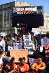 Benton Harbor High School students gather for a group photo in front of the high school in Benton Harbor, Mich., Tuesday, June 11, 2019, during an annual Peace Walk held at the end of the school year.  The Benton Harbor School Board has released a plan aimed at keeping the district's high school open and avoiding a state-threatened shutdown of the struggling district.