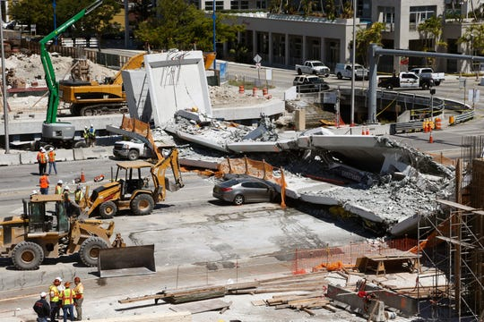 Crushed cars under a section of a collapsed pedestrian bridge near Florida International University in the Miami area on March 16, 2018