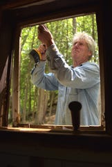 Carl Fromholtz removes a window frame at the Paradise Pines Resort. The resort has re-opened a mile south of the village of Elk Rapids, offering small cabins that have been remodeled and modernized.