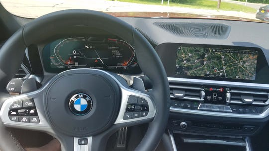 The steering wheel is fat on the 2019 BMW 330i for good grip on track - but the graphics are lovely for tooling around town.