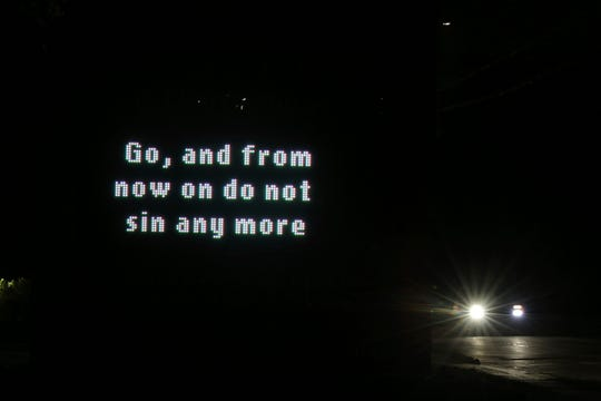 """An illuminated sign outside St. Michael Archangel Catholic Church in Houston reads, """"Go, and from now on do not sin any more"""" on April 11, 2019. The church, which has been grappling for decades with the sexual abuse of children, is now being forced to reckon with the recognition that adults too can be sexually exploited by clergy."""