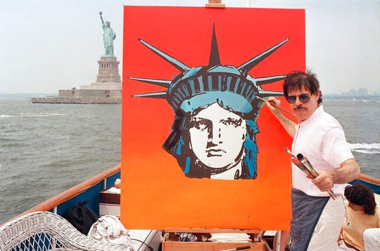 In this July 4, 1987, file photo, artist Peter Max works on a painting of the Statue of Liberty aboard a boat in New York Harbor, as part of the Fourth of July festivities New York.