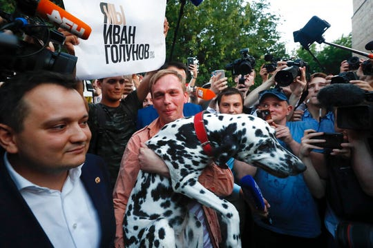 Prominent Russian investigative journalist Ivan Golunov, carry his dog as he leaves a Investigative Committee building in Moscow, Russia, Tuesday, June 11, 2019. In a surprising turnaround, Russia's police chief on Tuesday dropped all charges against Golunov whose detention sparked public outrage and promised to go after the police officers who tried to frame the journalist as a drug-dealer.