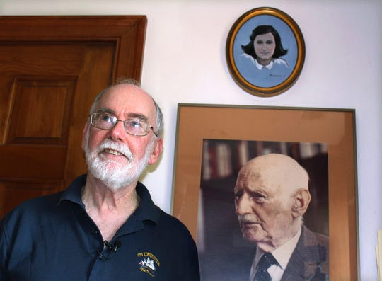 Ryan Cooper stands next to a photo of Otto Frank, the father of the famed Holocaust victim and diarist Anne Frank, at his home in Yarmouth, Mass.