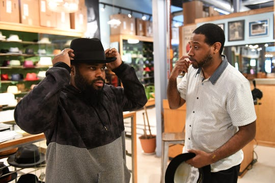 Employee Jovon Garrison, right, helps customer Jerome Dearing, 34, of Detroit find a hat at the store's new home in a former meatpacking warehouse at 2472 Riopelle.