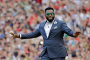 "Boston Red Sox baseball great David Ortiz waves to fans June 23, 2017, at Fenway Park in Boston as the team retires his number ""34"" worn when he led the franchise to three World Series titles."