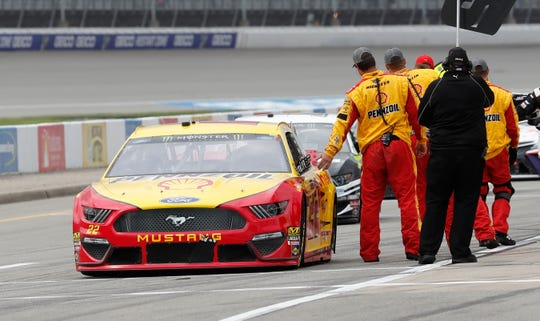 Joey Logano gets a high five from a pit member before Monday's race.