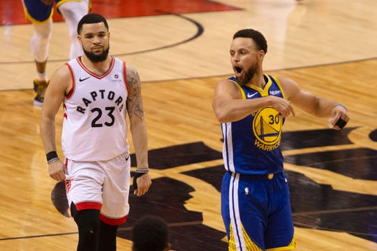 The Golden State Warriors' Stephen Curry celebrates in front of the Toronto Raptors' Fred VanVleet at the final buzzer.