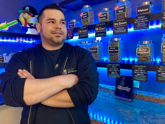 In this April 8, 2019, photo, Roberto Gonzalez, the general manager of Western Oregon Dispensary in Sherwood, Ore., poses for a photo in front of jars of medical marijuana.