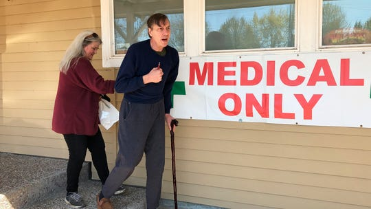 In this April 26, 2019, photo, medical marijuana cardholder Scott Donnelly, assisted by his wife and licensed caregiver, Vicki Poppen, leaves Western Oregon Dispensary in Sherwood, Ore., after buying medical marijuana to treat muscle spasms caused by his multiple sclerosis.